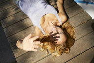 Happy blond woman lying on wooden jetty in sunshine - PNEF01054