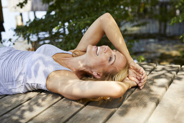 Happy blond woman lying on wooden jetty at a lake - PNEF01057