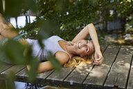 Happy blond woman lying on wooden jetty at a lake - PNEF01060
