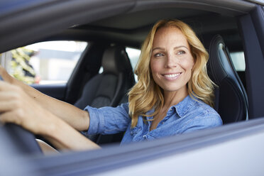 Smiling woman driving car looking out of window - PNEF01063
