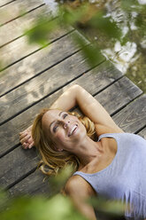 Happy blond woman lying on wooden jetty at a lake - PNEF01066