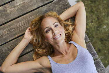 Portrait of smiling blond woman lying on wooden jetty at a lake - PNEF01069
