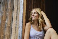 Smiling blond woman in front of wooden hut - PNEF01072