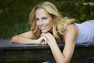 Portrait of smiling blond woman lying on wooden jetty - PNEF01078
