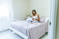 Pregnant woman sitting on the bed using laptop - KIJF02038