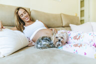 Dog lying next to pregnant woman on the couch at home - KIJF02056