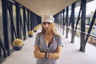 Portrait of attractive young woman standing in arcade wearing leopard print dress - RSGF00021