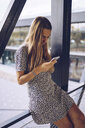Attractive young woman in leopard print dress checking cell phone - RSGF00024