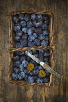 Wicker basket of organic plums, wooden table - LVF07462