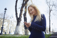 Smiling blond woman using smartphone in the city - AZF00101