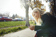 Smiling blond woman using smartphone outdoors - AZF00107
