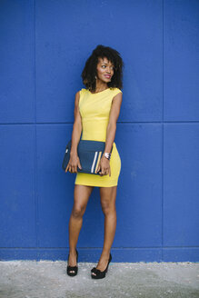 Portrait of fashionable businesswoman with laptop bag standing in front of blue wall - FMGF00063
