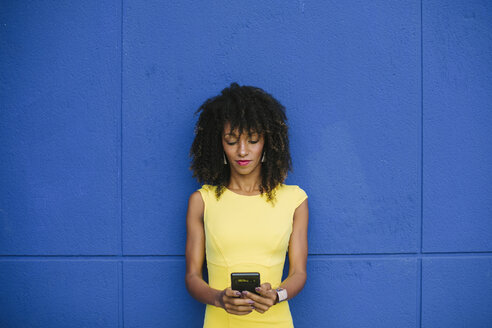 Portrait of fashionable businesswoman in yellow dress text messaging against blue background - FMGF00066