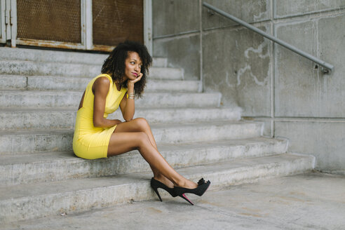 Fashionable businesswoman in yellow dress and high heels sitting on stairs - FMGF00069