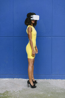 Woman in yellow dress wearing Virtual Reality Glasses against blue background - FMGF00072