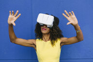 Woman using Virtual Reality Glasses against blue background - FMGF00075