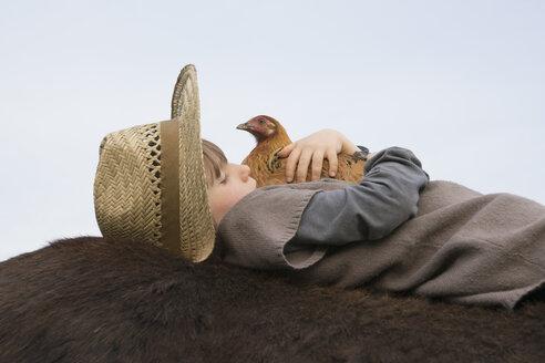 Girl hugging chicken, laying on horse - FSIF03346