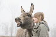 Girl standing next to donkey - FSIF03355