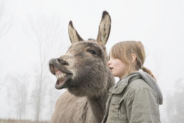 Girl standing next to donkey - FSIF03355