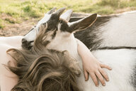 Girl hugging goat - FSIF03367