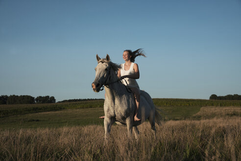 Girl riding horse in sunny, rural field - FSIF03391