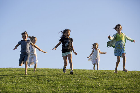 Happy siblings running on grassy field against clear blue sky at park - CAVF49116