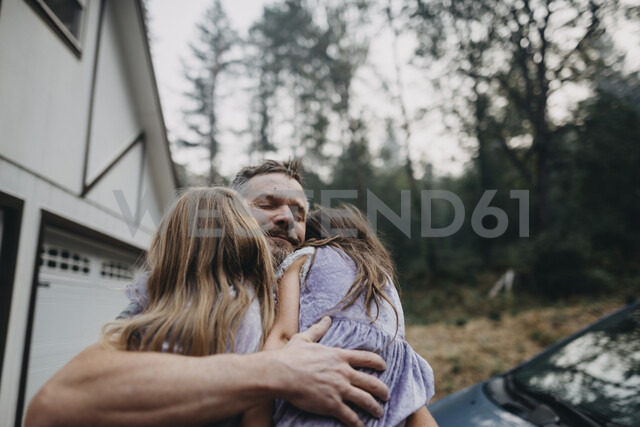 Father embracing daughters while standing in forest - CAVF49122