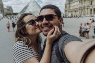 Portrait of girlfriend kissing boyfriend against Musee du Louvre in city - CAVF49134