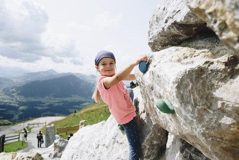 Portrait of girl rock climbing against sky - CAVF49140