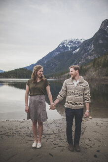 Full length of smiling young couple holding hands while standing on lakeshore at Silver Lake Provincial Park - CAVF49155