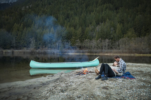 Full length of couple resting by campfire on lakeshore at Silver Lake Provincial Park - CAVF49161