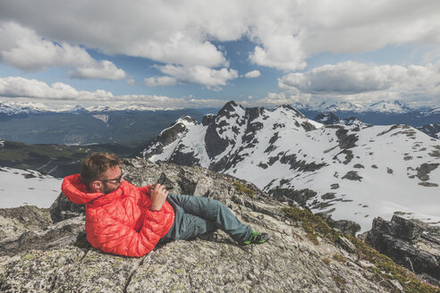 Full length of hiker using smart phone while resting on mountain against cloudy sky during winter - CAVF49164