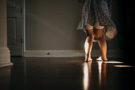 Low section of girl standing on floor at home - CAVF49206