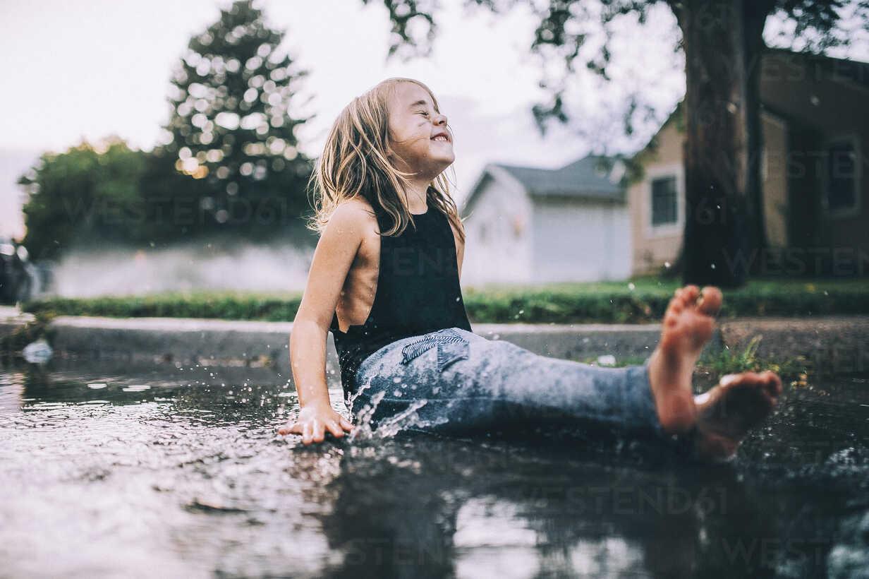 Happy girl sitting on wet street during rainy season - CAVF49209 - Cavan Images/Westend61