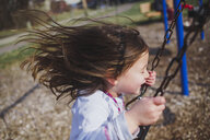 Side view of playful girl swinging at playground - CAVF49212
