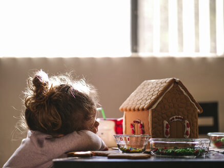 Girl resting by gingerbread house on table at home - CAVF49221