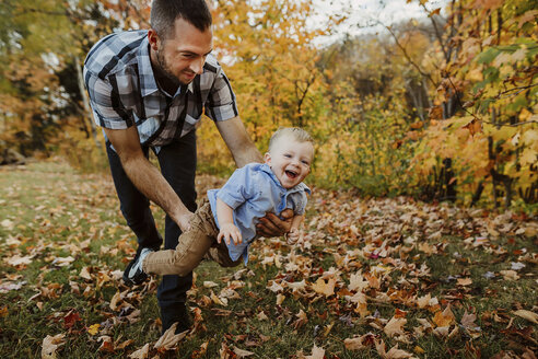 Father playing with son while standing on grassy field in forest during autumn - CAVF49227
