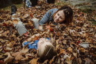High angle view of happy mother with son lying on autumn leaves in forest - CAVF49230