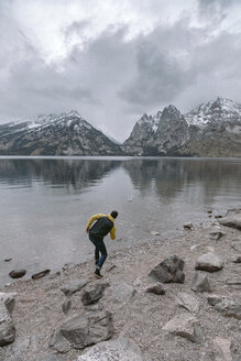 Full length of playful man throwing stone in lake against mountains and cloudy sky during winter at Grand Teton National Park - CAVF49272