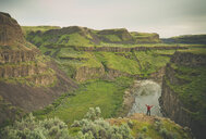 Rear view of man with arms outstretched standing at Palouse Falls State Park - CAVF49275