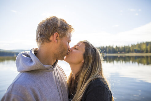 Loving couple kissing on mouth against lake - CAVF49281