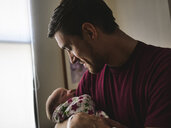 Father looking at newborn son sleeping at hospital - CAVF49323
