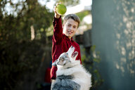 Boy playing with dog while standing at yard - CAVF49341