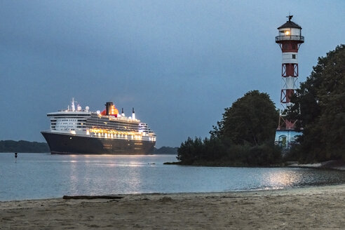 Germany, Hamburg, Hamburg-Rissen, Lighthouse Wittenbergen, Cruise ship Queen Mary 2 on Elbe river at blue hour - KEB00957