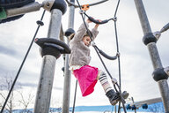 Low angle view of girl climbing on rope against cloudy sky at playground - CAVF49375