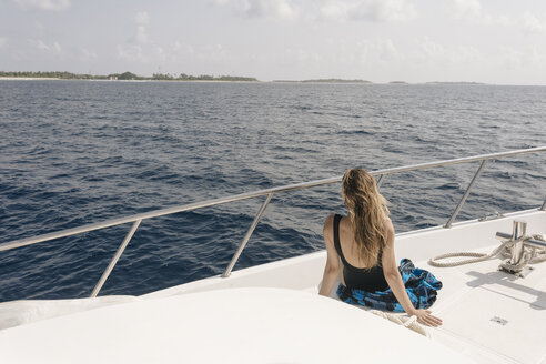 Rear view of woman looking at sea while traveling in yacht against sky during sunny day - CAVF49384