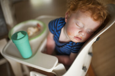 High angle view of cute baby boy with food and drink sleeping on high chair at home - CAVF49396