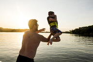Rear view of shirtless father throwing son in lake against clear sky during sunset - CAVF49399