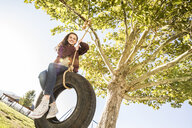 Low angle portrait of smiling girl sitting on tire swing hanging from branch at park during sunny day - CAVF49414