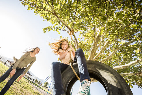 Low angle view of girl pushing friend sitting on tire swing at park - CAVF49417